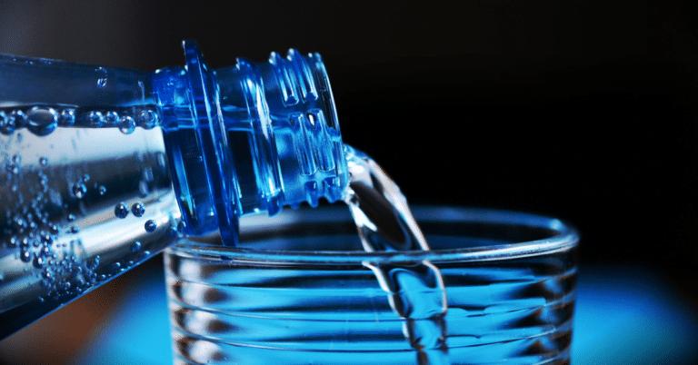 Garrafa de agua azul a verter para copo de vidro, ilustração de beber agua às refeições engorda?