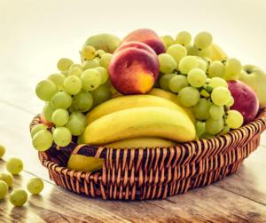 Cesta de verguinha com fruta com bananas, pessegos e uvas