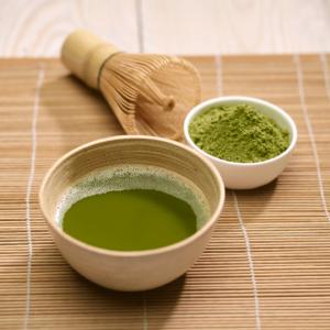 Chá verde matcha numa chavena de madeira, com pó de matcha numa chavena branca e um mexedor, em cima de um individual de mesa