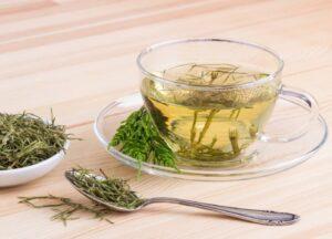 Chá de cavalinha com folhas de cavalinha, uma colher num tampo de madeira clara