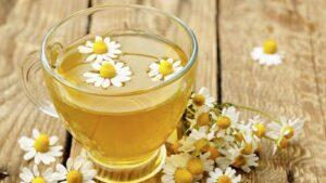Chá de camomila numa chavena de vidro transparente com flores de camomila dentro do copo e em cima da mesa de madeira