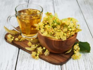 Chá de de tília numa chavena de vidro transparente com flores de tilia dentro de uma bowl de madeira