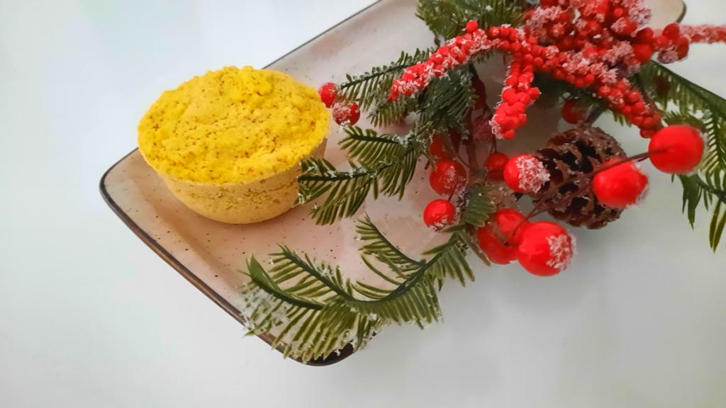 Bolo de laranja em caneca com arranjos florais de natal, travessa beje e colorido vermelho