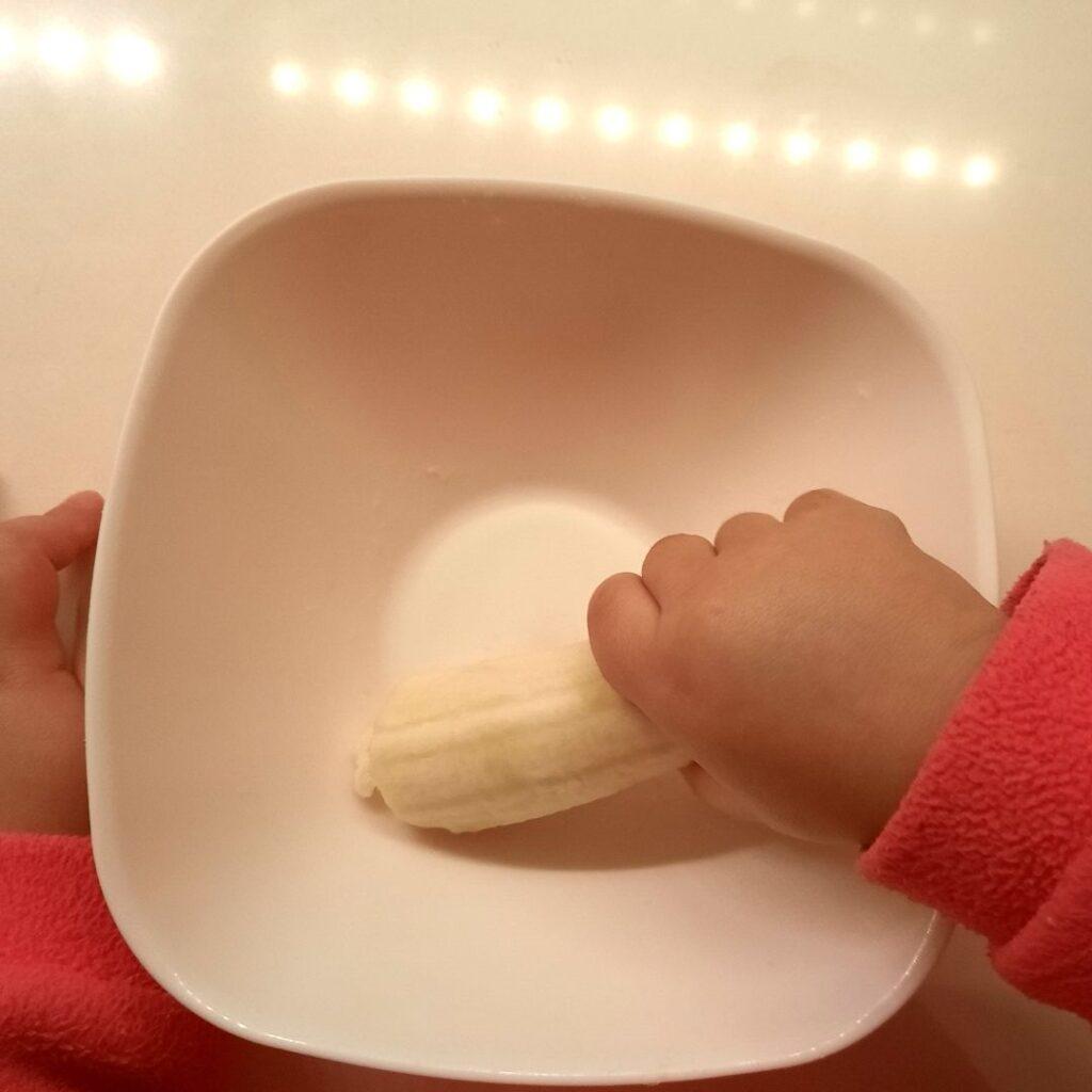 Triturar a banana para fazer papas de aveia no forno com banana